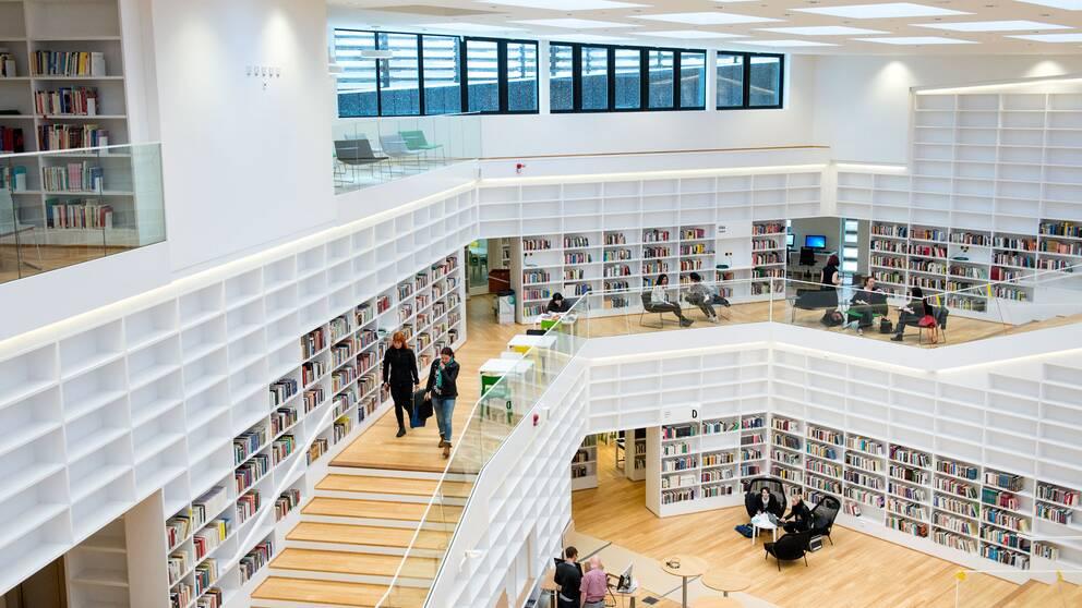 trappor och vita bokhyllor i öppen flerplanslösning.