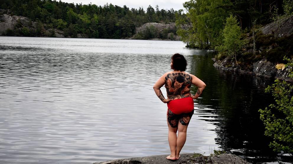 Kvinna står på klippa vid sjö i mulet väder