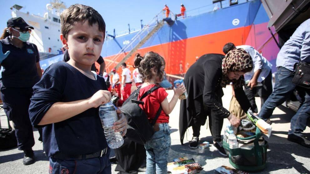 En liten pojke håller en vattenflaska och tittar in i kameran. I bakgrunden ses en flicka med ett juicepaket och en mamma som har mat i en korg. Lång bort ses flera människor iklädda röda byxor med vita t-shirtar med röda korset-loggan på ryggen.