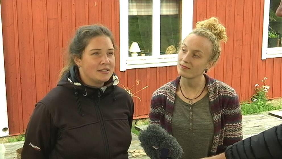 två tjejer framför falurött hus