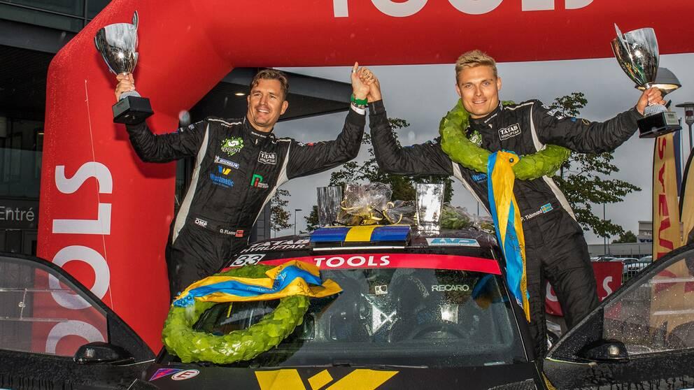 Postus Tidemand och Jonas ANdersson står vid sin bil, efter vinst i rally-SM