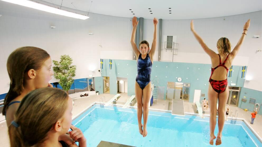 Barn på simhoppsträning, två tjejer hoppar ner i bassängen