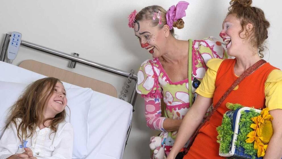 clownerna Gajans och Boel Betula som skrattar tillsammans med flickan i sängen. Fotografen heter Christin Philipson.