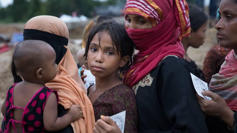 Aziza är nio år och kom till det provisoriska lägret för två dagar sen. Nu står hon längst bak i den långa kön med en matkupong i handen.