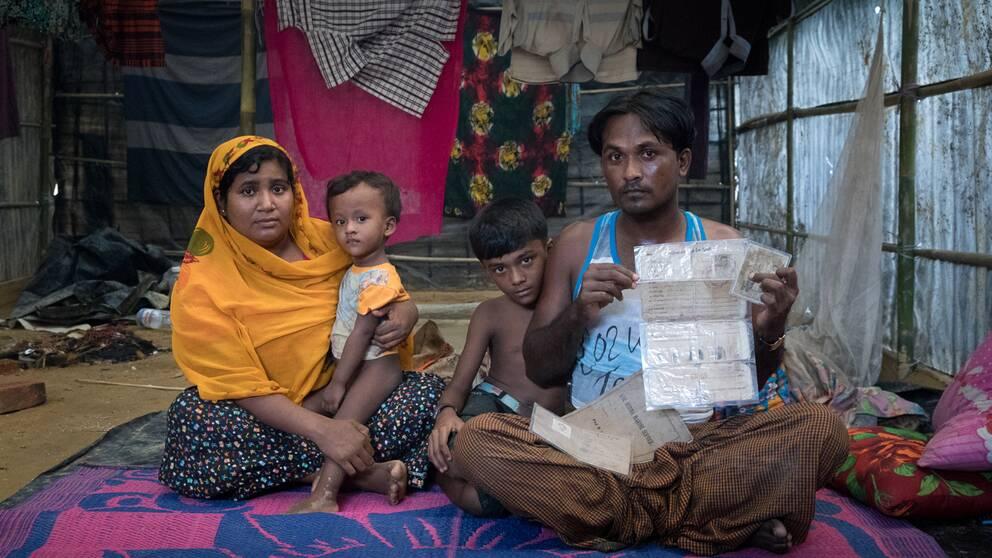 Mohammed Rofique med familj visar upp ett dokument som visar hur hans far tjänstgjorde i den burmesiska armén i 18 år – nu har han fått fly därifrån.