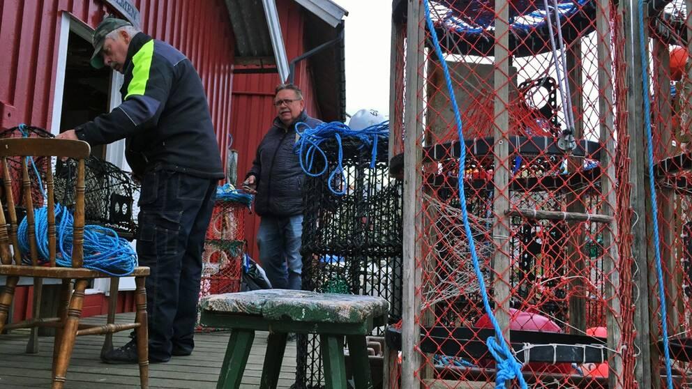 Två män står och pysslar med hummertinor.