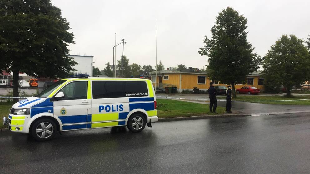 Polisbil i front, gul lokal i bakgrunden.