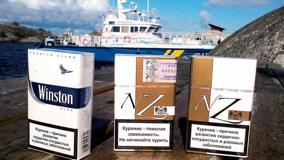 Cigarettförpackningar framför Kustbevakningens båt.