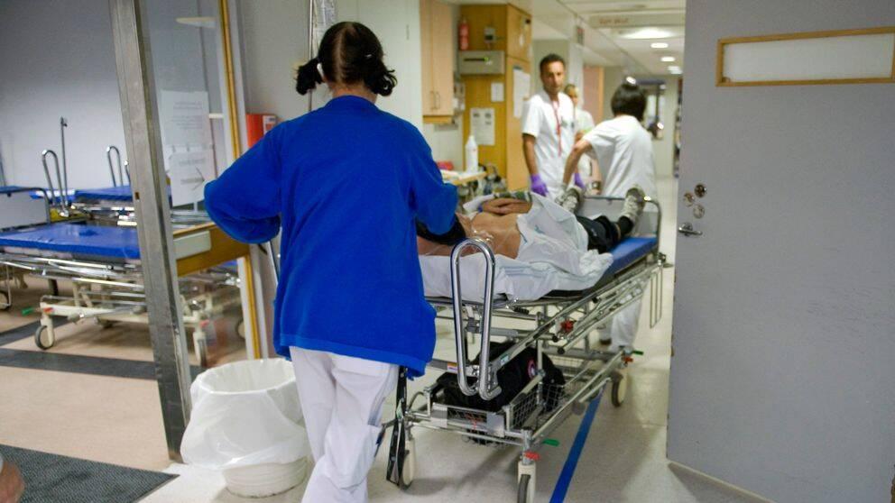 Vårdpersonal springer med en person som ligger på en sjukhussäng.