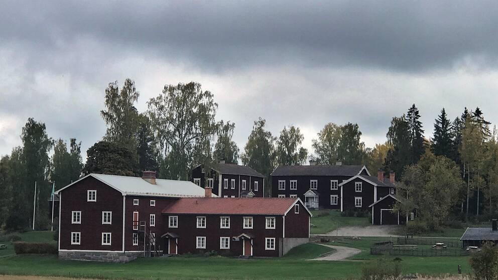 vy över gammal gård med träbyggnader