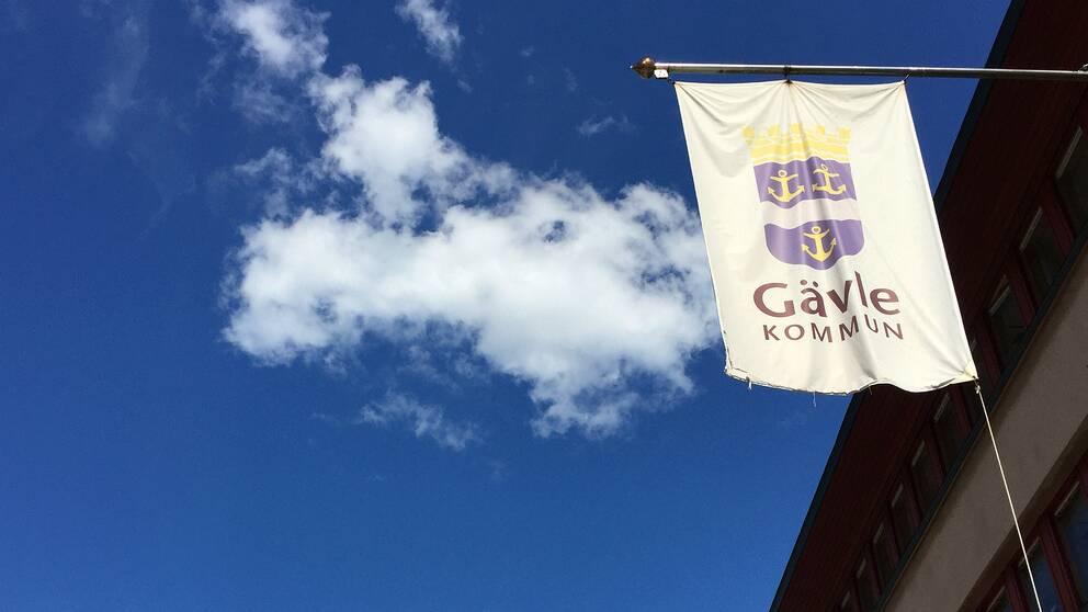 kommunflagga på byggnad, vy mot himlen