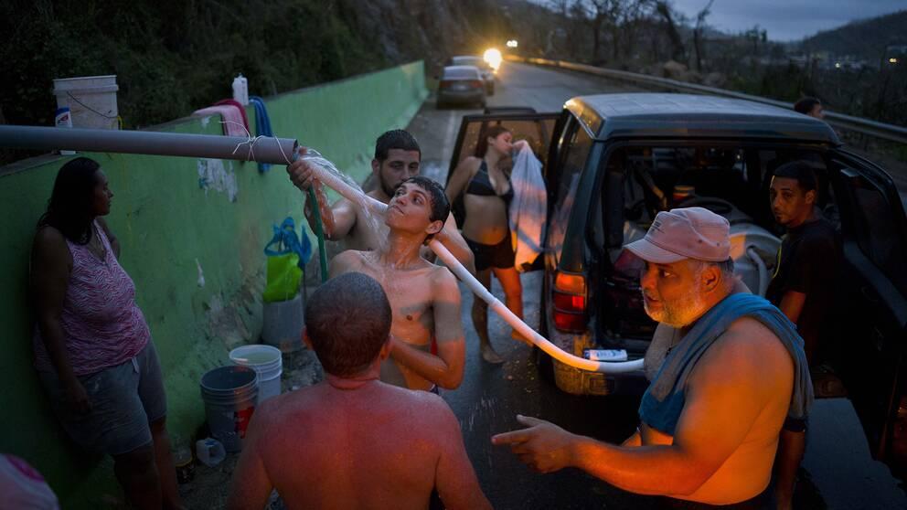 Människor i samhället Naranjito i Puerto Rico hämtar vatten från en bäck. Många är utan el och vatten efter orkanens härjningar.
