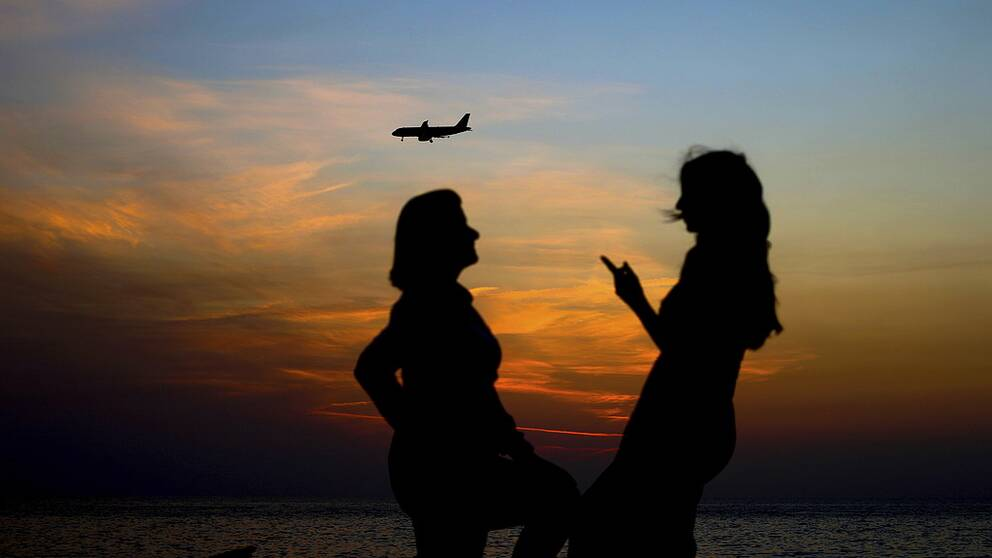 Women share a moment as a passenger plane comes in for a landing at Beirut International Airport while the sun sets behind the Mediterranean Sea in Beirut, Lebanon, Thursday, Nov. 10, 2016. (AP Photo/Hassan Ammar)