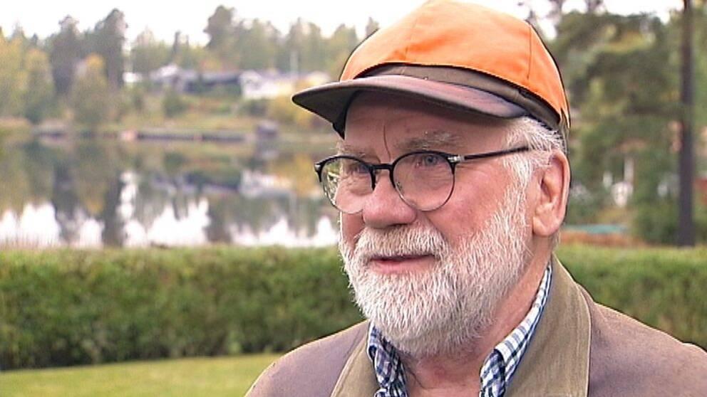 äldre man med glasögon och jakt-keps