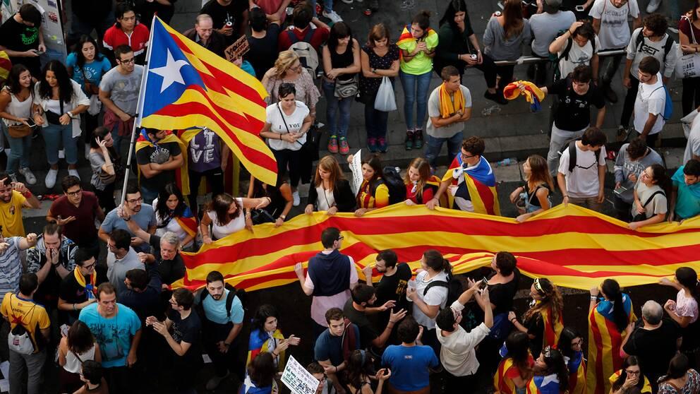 Demonstranter håller upp den katalanska flaggan.