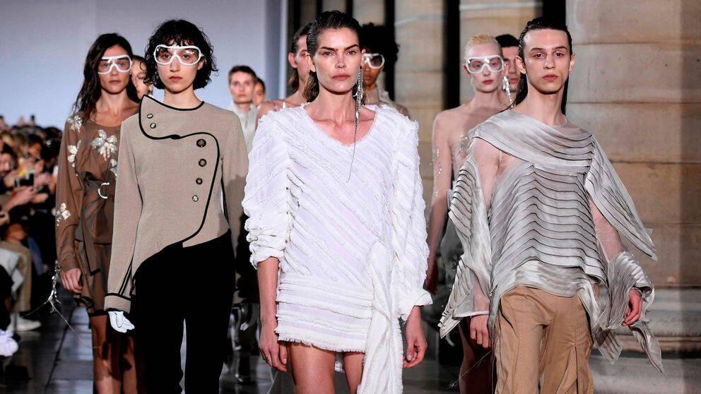 Manliga och kvinnliga modeller på en catwalk i Paris.