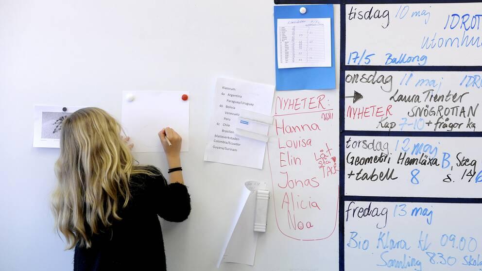 En elev redovisar ett skolarbete vid en whiteboardtavla i ett klassrum. ARKIV.