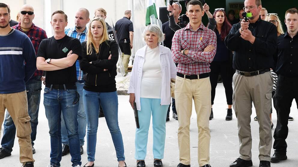 en grupp människor står uppställda med en gammal kvinna i mitten.