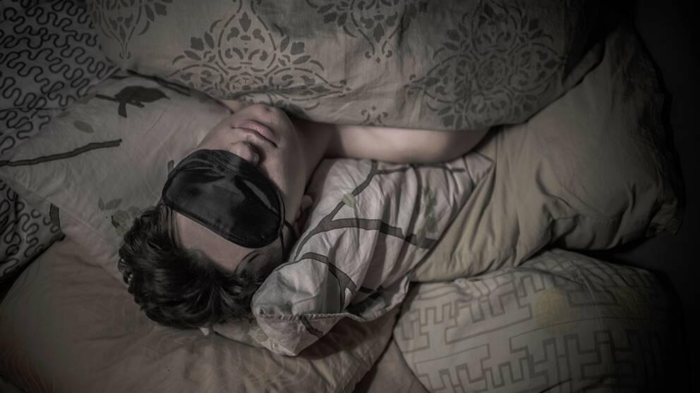 En man med sovmask i sängen.
