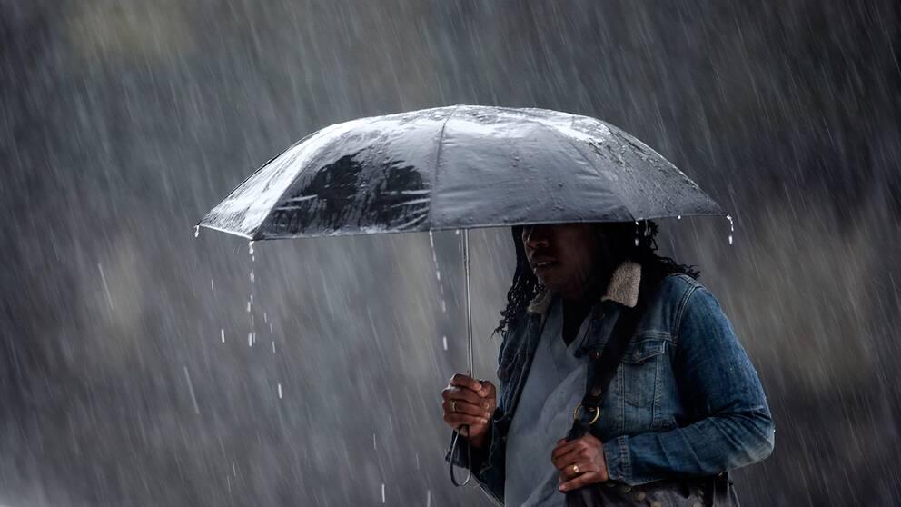 kvinna med paraply i ösregn