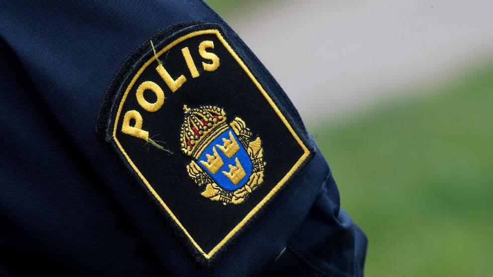 Polismärke på ärm på uniform.