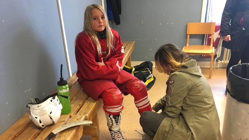 Alma Bååth, Nora HC, får hjälp med skridskorna.