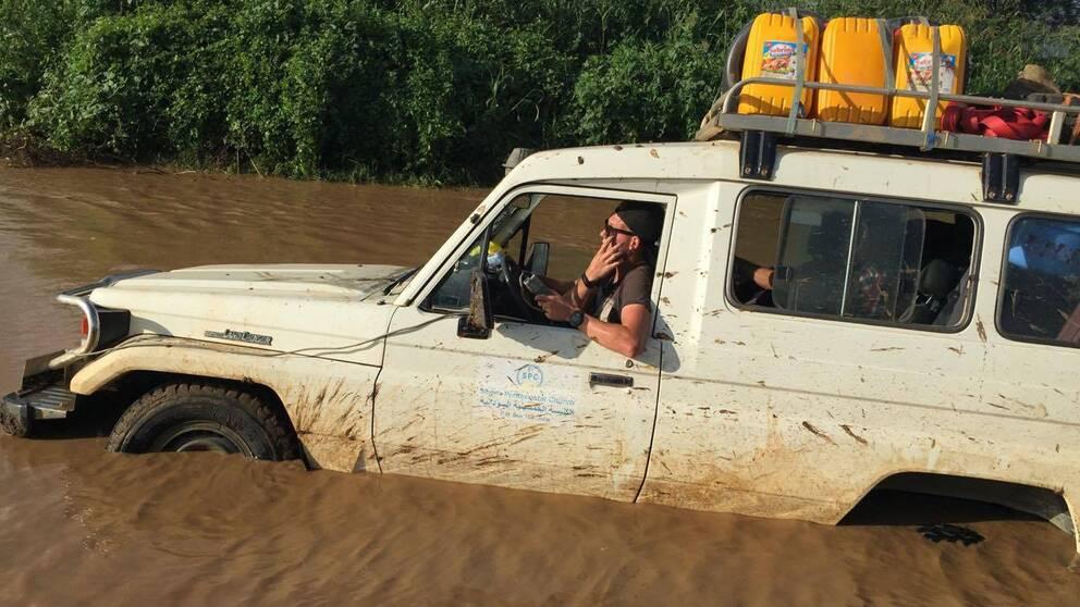 Efter att ha fått loss den ur leran färdas reporterteamet längs med den vattendränkta vägen.