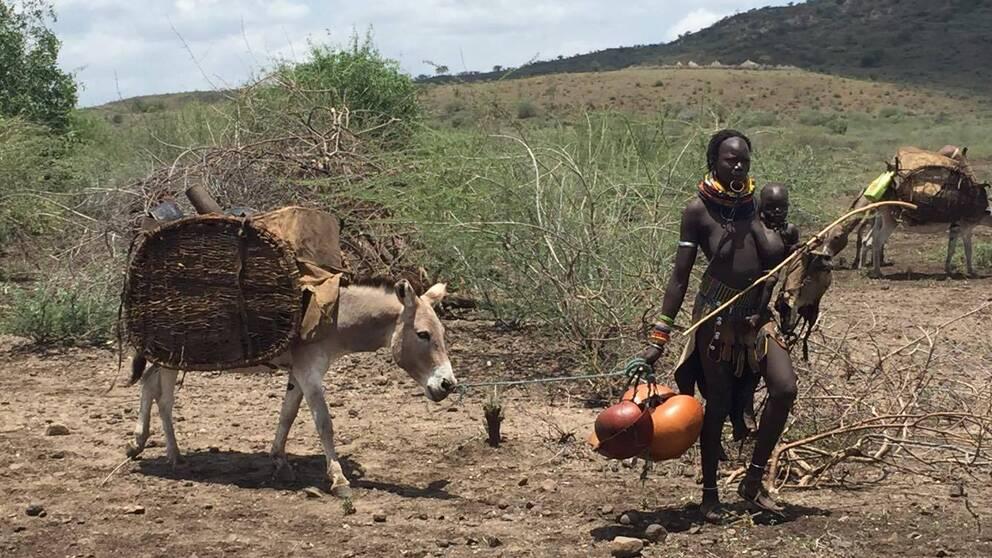 En kvinna bär på ett barn och drar en åsna med last bakom sig.