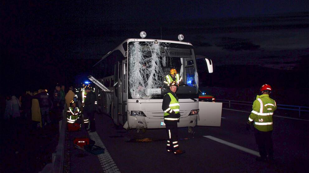 Vit buss med stora skador på framrutan. Räddningspersonal. Människor håller om varandra vid sidan av motorvägen.