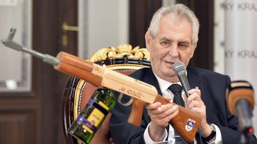 """Tjeckiens president Milos Zeman med en låtsas-automatkarbin märkt """"För journalister""""."""