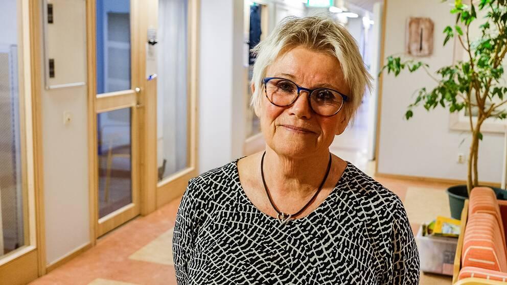 Kvinna med glasögon i en korridor