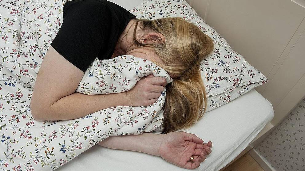 Kvinna som gömmer sitt ansikte med ett täcke