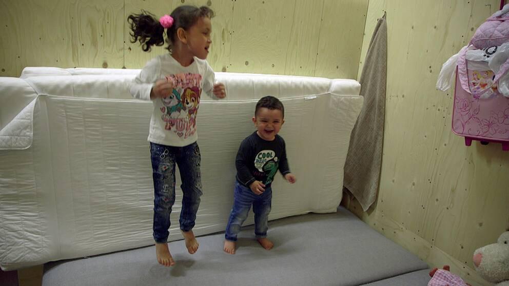 Barn som hoppar i en säng i bilhallen.