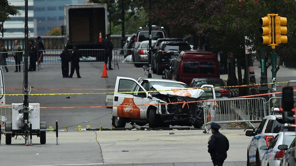 """A police offier walks past the wreckage of a Home Depot pickup truck, a day after it was used in an terror attack, in New York on November 1, 2017. The pickup truck driver who plowed down a New York cycle path, killing eight people, in the city's worst attack since September 11, was associated with the Islamic State group but """"radicalized domestically,"""" the state's governor said Wednesday. The driver, identified as Uzbek national named Sayfullo Saipov was shot by police in the stomach at the end of the rampage, but he was expected to survive. / AFP PHOTO / Jewel SAMAD"""