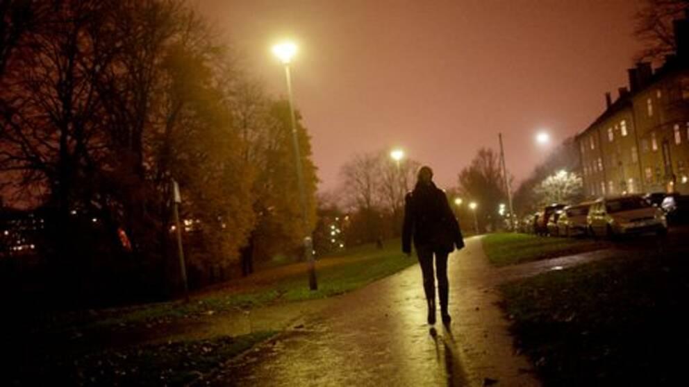 Kvinna går på gångväg i ett mörkt bostadsområde. Lampor lyser upp vägen.