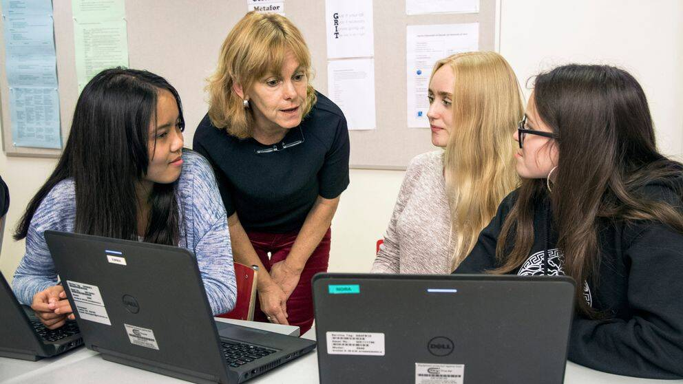 Tre elever tittar på sin lärare som står mellan dem och pratar.
