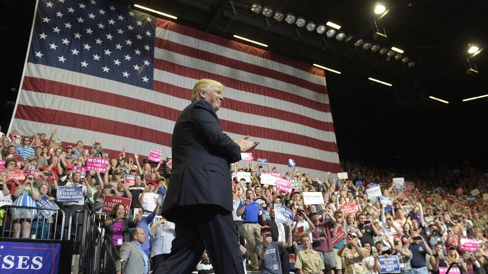Donald Trump på scen framför en grupp hejande anhängare.