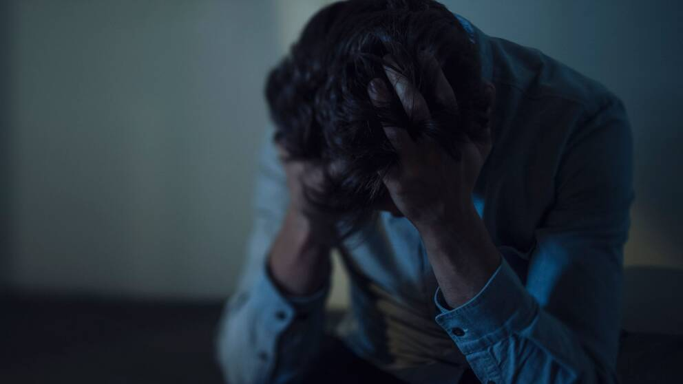 Man sitter i ett mörkt rum, håller sig för huvudet med fingrarna i håret.