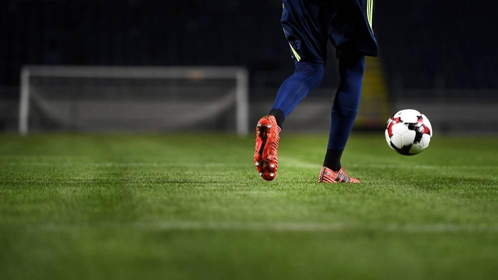 En man med en fotboll framför ett mål.