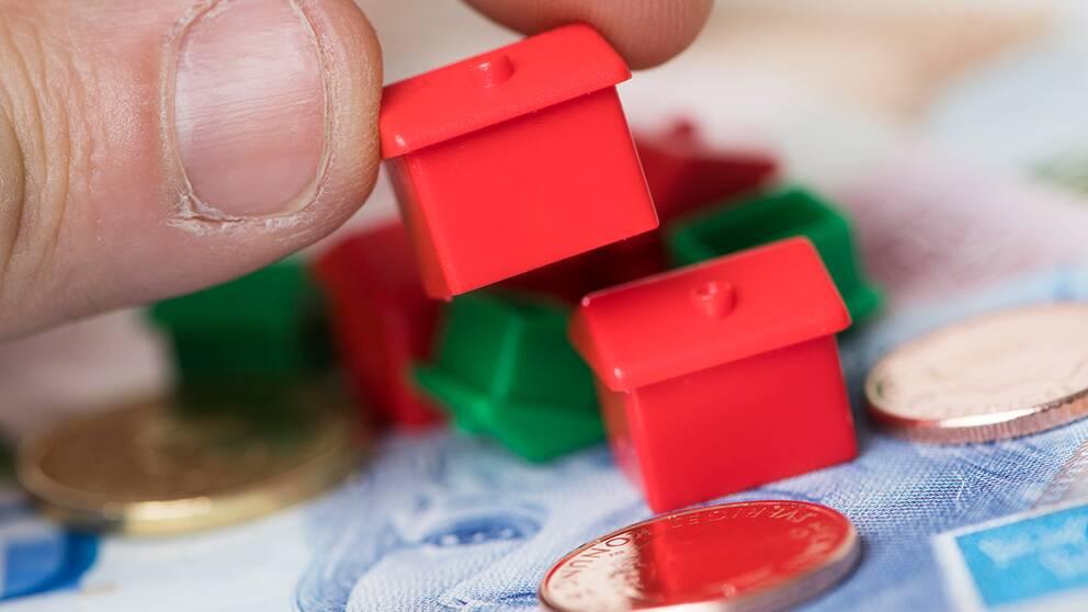 Hus i form av spelpjäser, mynt och sedlar