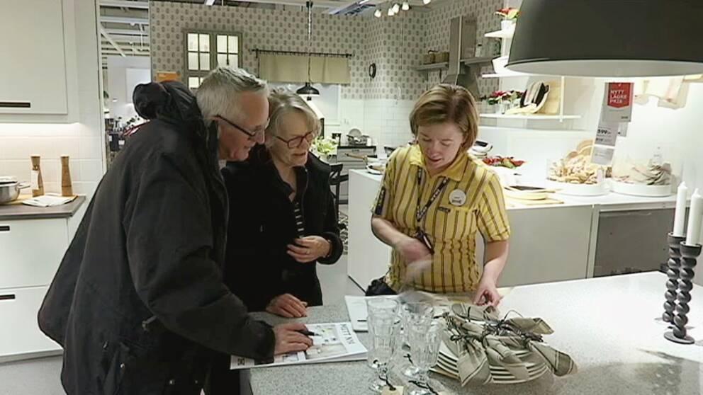 äldre par tittar i katalog tillsammans med anställd, i utställningskök på Ikea