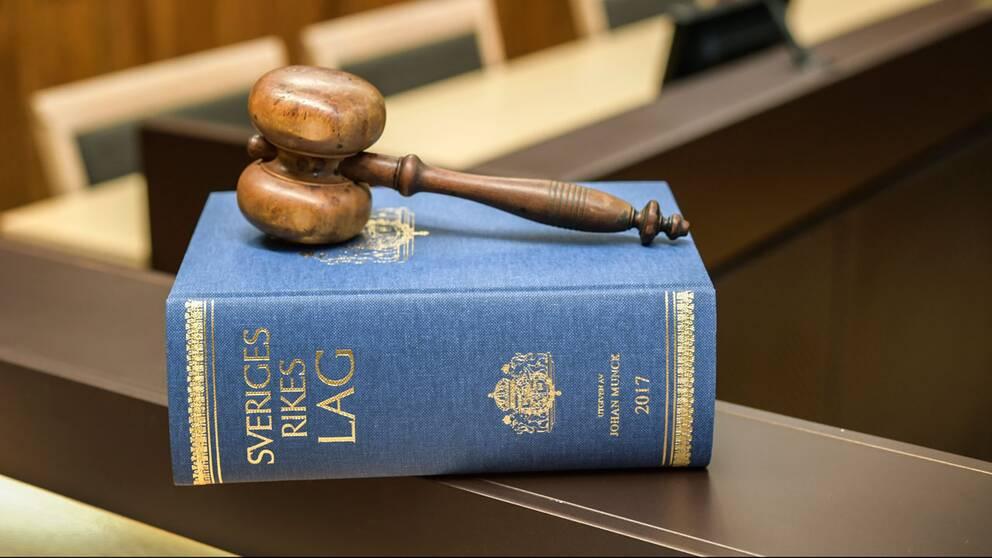 Domstolsklubba liggandes på lagbok i rättssal