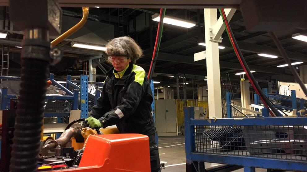 En kvinna står i verkstadsmiljö och arbetar