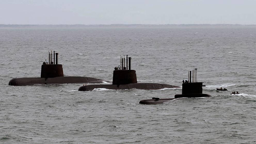 Tre ubåtar som stigit upp till ytan syns på rad i havet.