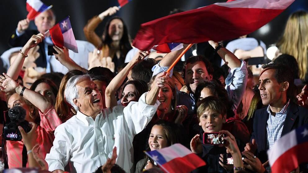 Sebastian Piñera står och vajar en stor chilensk flagga i publikhav.
