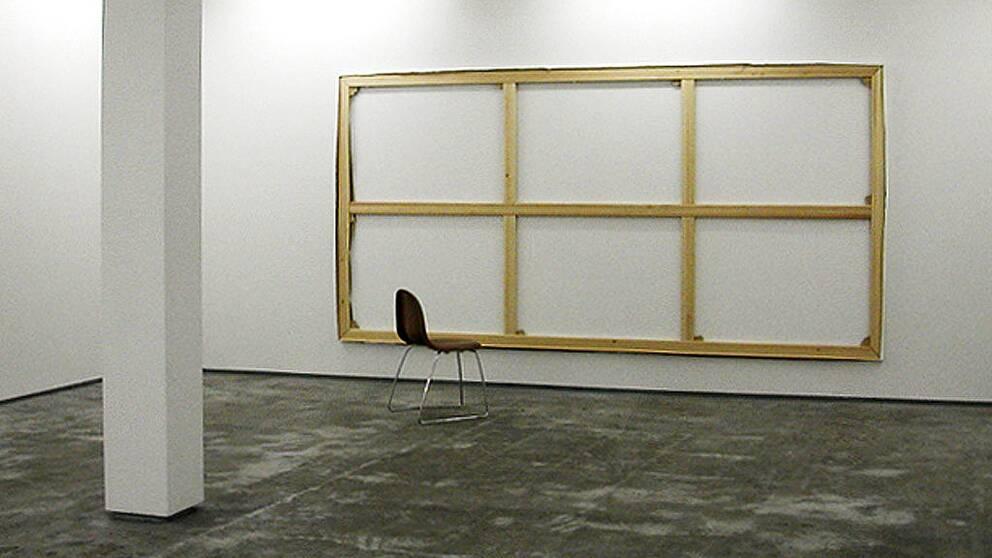 Ett vitt rum, på väggen hänger en stor träram, framför står en brun stol.