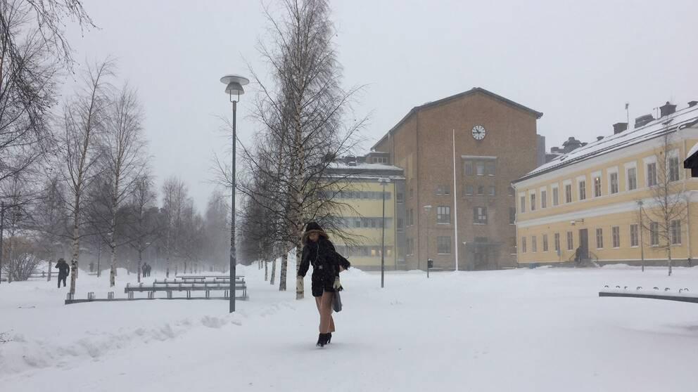 Kvinna går framåtlutad i snöstorm, skola i bakgrunden