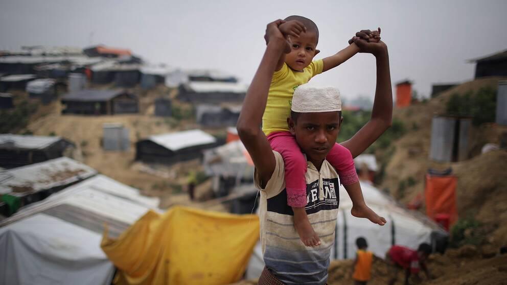 En rohingya pojke bär ett barn på sina axlar i flyktinglägret Jamtoli i Bangladesh.