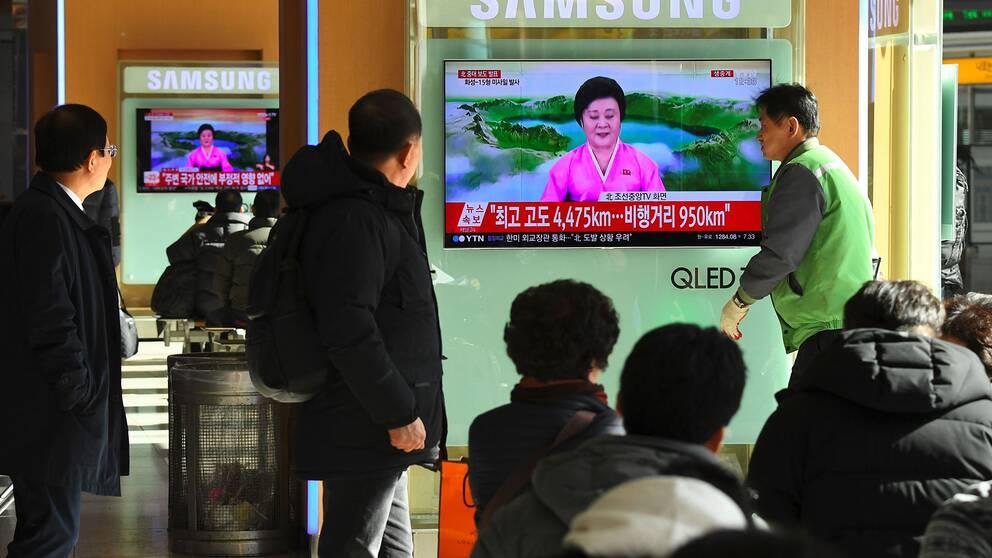 Människor ser en nordkoreansk tv-sändning kring uppskjutandet på en skärm i Sydkoreas huvudstad Seoul.