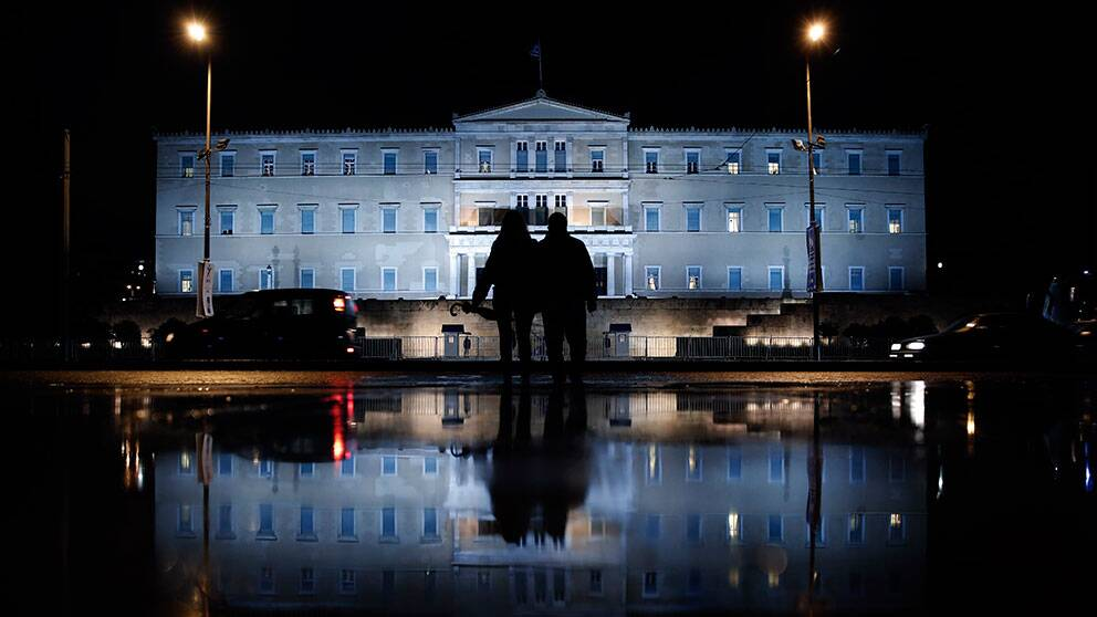 The illuminated Greek Parliament building ahead of the Nov. 14 World Diabetes Day, is reflected on a rain-soaked pavement as a couple wait to cross a street in Athens on Monday, Nov. 11, 2013. (Petros Giannakouris)